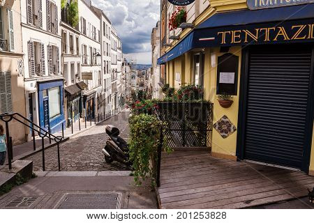 Paris, France - August 10, 2017. Old narrow street of cobblestone, shutter windows and flower pots on the Montmartre historic district by sunny day.