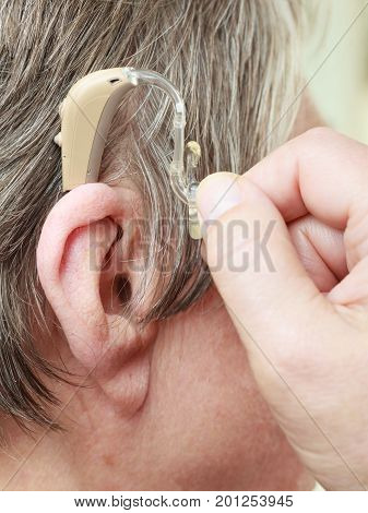 Closeup senior woman with hearing aid in her ear. Health care hear amplify device for the deaf.