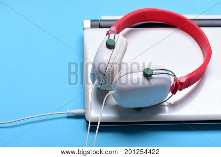 Sound recording idea. Headphones and silver laptop. Earphones made of plastic with computer. Music and digital equipment concept. Electronics isolated on light blue background with copy space