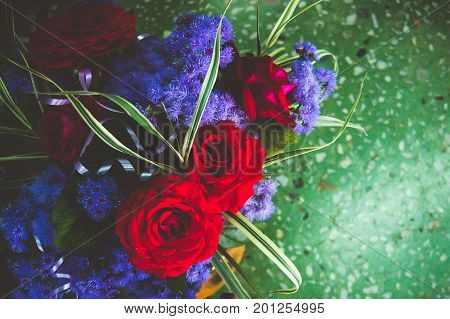 Red Roses With Blue Flowers In The Bouquet On The Background Of Green Marble