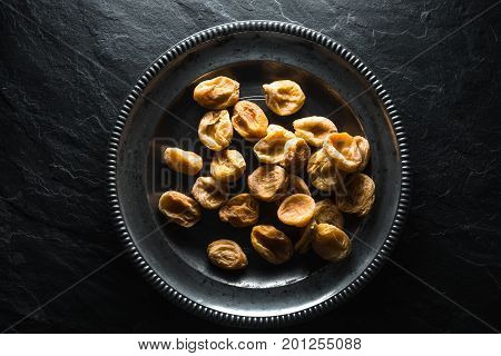 Dry dried apricots on a tin plate on a stone background horizontal
