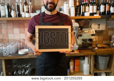 small business, people and service concept - happy man or waiter with blank blackboard at bar