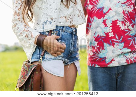 summer, fashion and people concept - close up of young hippie couple outdoors