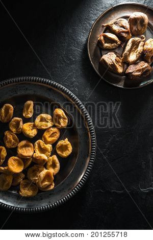 Dried figs and dried apricots on tin plates on a stone table vertical