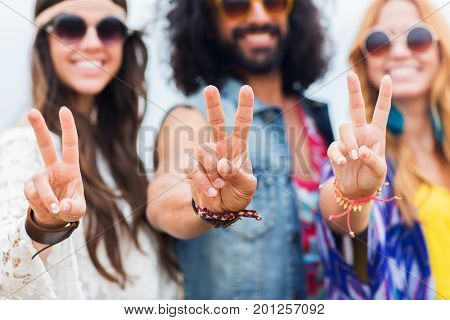 youth culture, gesture and people concept - smiling young hippie friends in sunglasses showing peace hand sign outdoors
