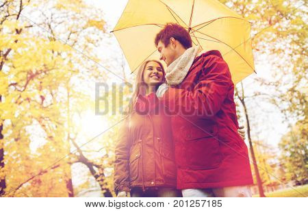 love, relationship, season, family and people concept - happy couple with umbrella walking in autumn park