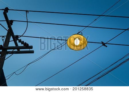 Lamps on the wires in daybreak and birds are out.