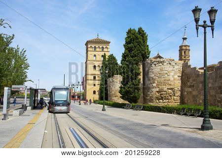 ZARAGOZA, SPAIN - AUGUST 19, 2017: A tram car passing through the Cesar Augusto avenue in Zaragoza, Spain, next to the remains of the ancient roman stonewall of Caesaraugusta, the roman city