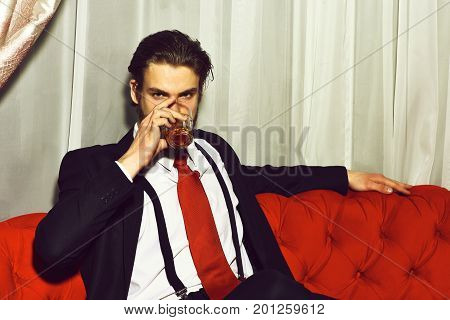 bearded man businessman long beard brutal caucasian hipster with moustache holding glass with whiskey has serious face unshaven guy with stylish hair in suit and red tie sitting on sofa