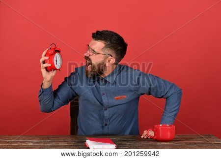 Cup, Retro Clock And Red Book On Vintage Desk