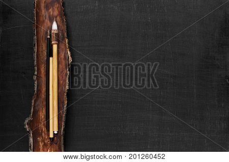 Black wooden background with Chinese paint brashes