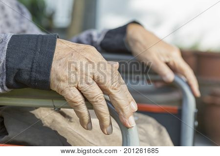 Elderly hands on a wheelchair at home