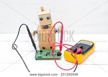 The robot holds a voltmeter in its hands and a printed circuit board is next to it. Horizontal photo