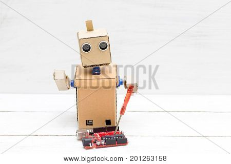 The robot holds a screwdriver and a printed circuit board