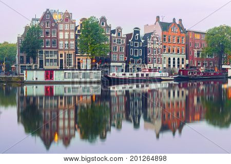 Amsterdam canal Amstel with typical dutch houses and houseboat from the boat in the morning, Holland, Netherlands.