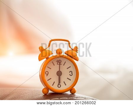 Orange Alarm clock on bed in morning with sun light