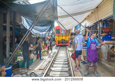 Samut Songkhram Province, Thailand - August 08, 2017: People are picked up the food for dodge the train are traveling across the market in Maeklong market,Thailand.
