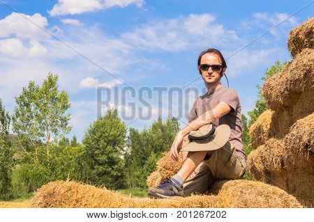 Handsome Man With Hat Sitting On Straw Bales And Looking To The Camera.