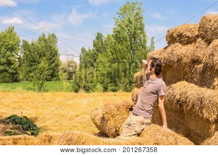Young Handsome Man Leaning Against The Straw Bales And Looking Away On A Sunny Day.