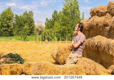 Young Handsome Man Resting On Straw Bales On A Sunny Day.