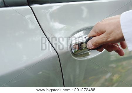 hand stabbing car key in handle hole and twist for open door