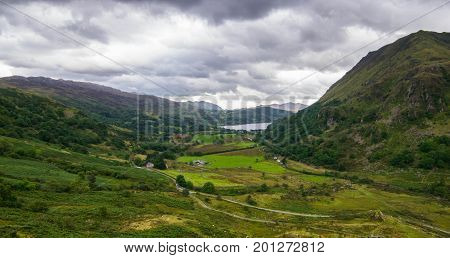 mountain lake and houses in Snowdonia National Park in North Wales of the United Kingdom. Snowdonia is a mountain range and a region in North of Wales.