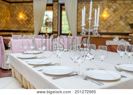 Table Setting With White Plates, Wineglasses, Candlestick And Cutlery On Tablecloths. Elegant Table