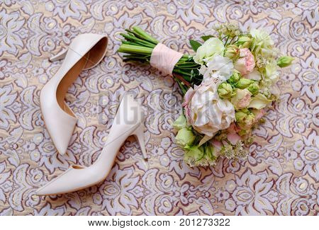 Close Up Of Beautiful Wedding Bouquet Of Pink And White Roses Lying Near Bride Shoes In Blur On Bed