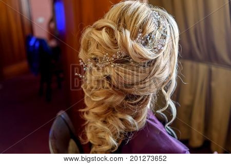 Beautiful bride fashion wedding hairstyle with jewelry back view. Blond girl with curly hair styling. Hairstyle for long hair with stylish hair accessory