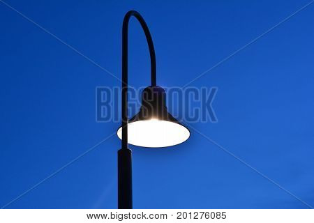 Black Lamp Post  With White Light  On Blue Twilight Sky Background