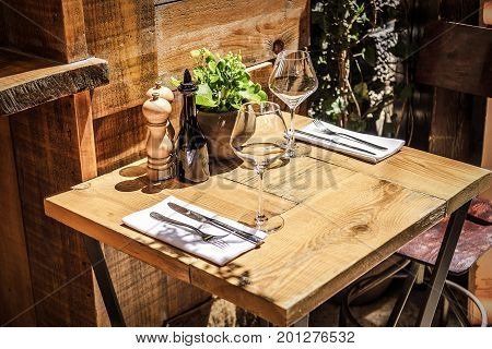Table in the restaurant in the open air with glasses of wine and serving.