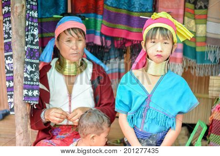 CHIANG MAI, THAILAND - July 10, 2017: Karen hill-tribe (Long Neck) woman weaving fabrics for a living at her house.