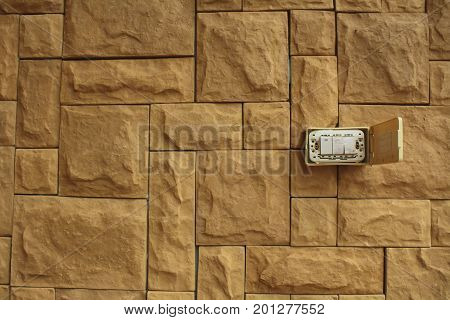 Old Power switch on the walls of the orange stone stacked beautifully White switch on the red brick wall