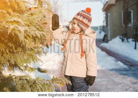 Portrait Of Cute Boy, Wearing In Warm Hat With Pom Pom In Cold Winter Day Playing Outdoor With Snow.