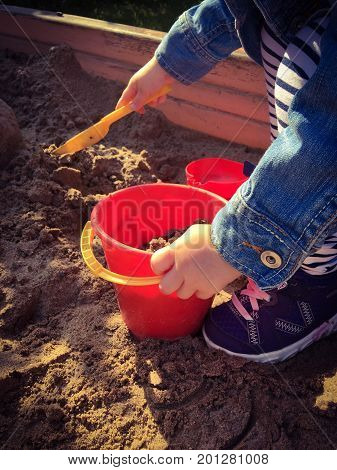 child playing in sandbox with showel and pail,