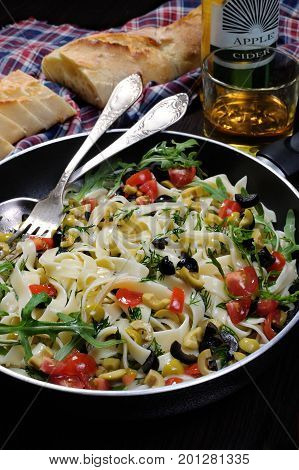 Pasta with crushed olives and cherry tomatoes arugula.