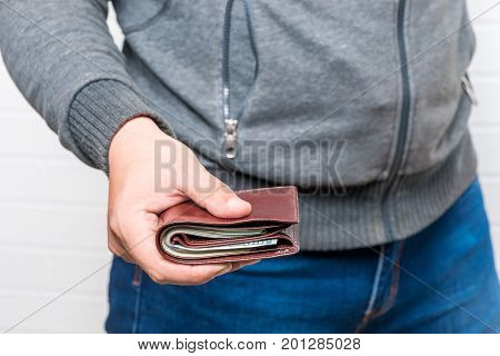 Man Holds A Brown Purse Full Of Money In His Hand