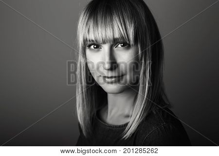 Closeup black-and-white portrait of beautiful young middle age blonde Caucasian woman looking in camera. Girl female with long blonde hair bob studio beauty shot.