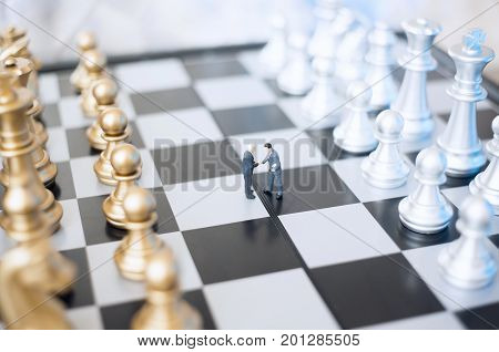 Two  toy businessmen, lawyers or politicians on a chessboard. Agreement concept.