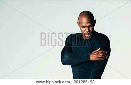 Portrait of handsome young men in gym t-shirt over grey background. African male model wearing compression t-shirt touching his bicep.