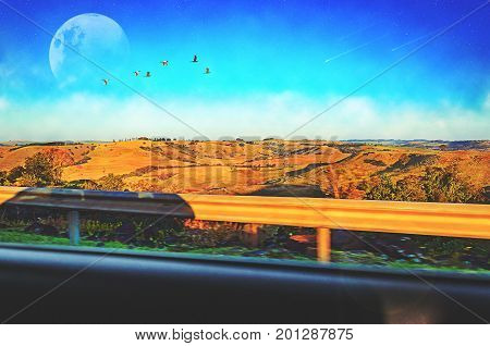 View from the car window of a landscape with farm fields hills a deep blue sky some clouds a big moon birds flying stars on sky and shooting stars falling. Fictional scene.