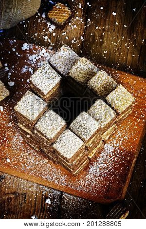 Wafer cookies built to an impossible penrose stairs which always goes upwards diet metaphor for eating more and more sweets rustic wooden background vertical
