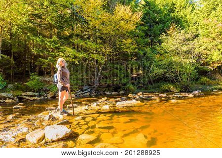Young Woman With Stick Crossing Red Creek River In Dolly Sods, West Virginia Smiling