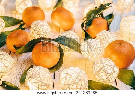 Mandarins with green leaves on a white wooden table. Twinkling lights on a table. Tasty tangerines for the New Year festive table
