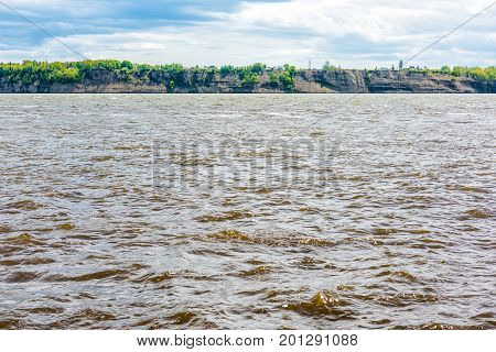 Cityscape or skyline of Sainte-Croix and view of cliffs by brown water Saint Lawrence river in Quebec Canada