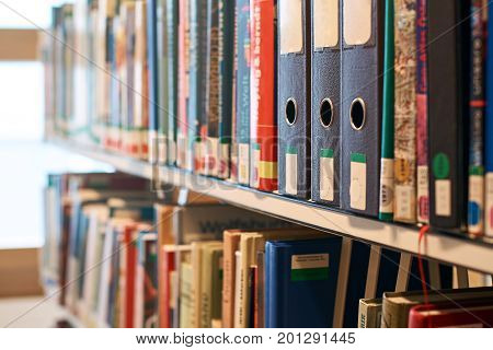 Box file folders with labels on a bookshelf in a library