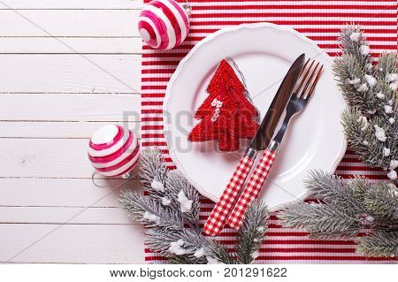 Christmas table setting. White plate knife and fork napkin and christmas decorations on white and red colors on white wooden table. Top view. Place for text. Selective focus.