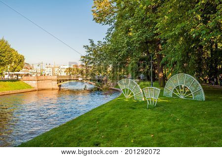 ST PETERSBURG RUSSIA - AUGUST 15 2017. City landscape of St Petersburg. Moika river and glass composition Fans of the Empress in the summer park of Michael Garden in St Petersburg Russia