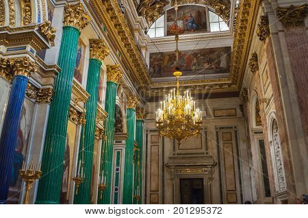 ST PETERSBURG RUSSIA - AUGUST 15 2017. Decoration details in the interior of the St Isaac Cathedral in St Petersburg Russia. Malachite columns and Bible paintings in St Petersburg landmark