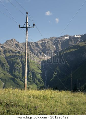 Scenic Alpine rocky alpine valley of Sportgastein in summer with row of power lines and electricity pole. Picturesque mountain pasturelands, great mountain massif and sunny weather.